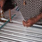 Artisanat du Cambodge, une artisane prépare avec doigté la chaîne des fils de soie naturelle pour le métier à tisser, pour de magnifiques écharpes.