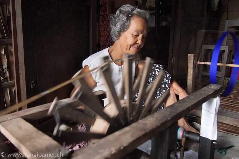 Artisanat équitable des villages du Cambodge, une artisane tisse sur un métier à tisser traditionnel, de magnifiques écharpes en soie naturelle Frangipanier