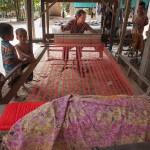 Artisanat équitable des villages du Cambodge, une artisane tisse sur un métier à tisser traditionnel de magnifiques écharpes en soie naturelle Frangipanier