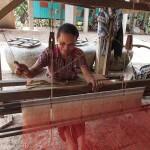 Artisanat équitable de villages du Cambodge, une artisane tisse sur un métier à tisser traditionnel de magnifiques écharpes en soie naturelle Frangipanier