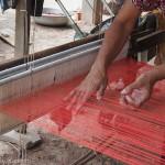 Artisanat équitable de villages du Cambodge, les mains d'une artisane oeuvrant sur un métier à tisser traditionnel, écharpes en soie naturelle Frangipanier.